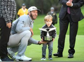 Dustin Johnson poses with his son and the trophy he won last year at the Genesis Open. He is a 5/1 pick to defend his title. (Image: LA Times)