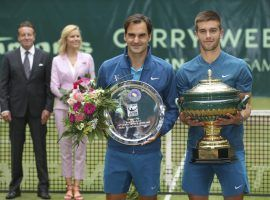 Borna Coric (right) holds his trophy after defeating Roger Federer (left) in the final of the Gerry Weber Open in Halle, Germany on Sunday. (Image: Friso Gentsch/DPA/AP)