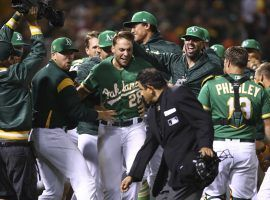 Matt Olson is mobbed by his teammates after he hit a walk-off home run to defeat Houston on Saturday. (Image: AP)