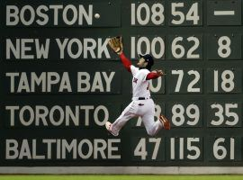 Boston Red Sox outfielder Andrew Benintendi leaps to make a catch in front of the Green Monster in the fifth inning of Game 2 of the 2018 World Series against the Los Angeles Dodgers. (Jim Davis/Boston Globe)