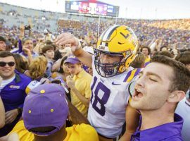 LSU fans storm the field to celebrate with the players, who upset No. 2 Georgia, 36-16. (Image: AP)