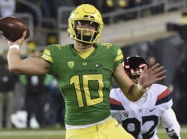 Quarterback Justin Herbert of the Oregon Ducks throwing a pass against Utah. (Image: Steve Dykes/Getty)