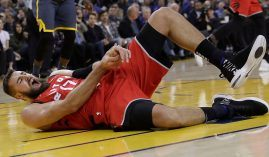 Toronto Raptors' center Jonas Valanciunas withers in pain after a hack job from the Golden State Warriors' Draymond Green. (Image: Jeff Chiu/AP)