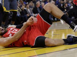 Toronto Raptors' center Jonas Valanciunas withers in pain after a hack job from the Golden State Warriors' Draymond Green. (Image: Jeff Chiu/AP)