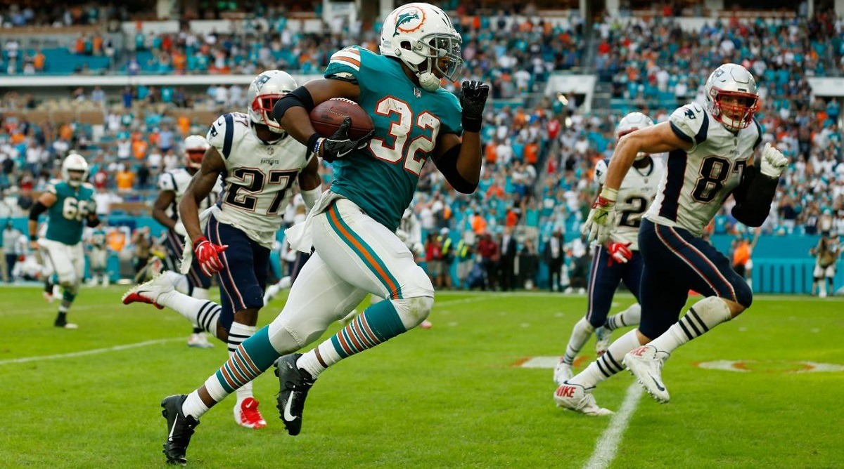 1631e5910 Running back Kenyan Drake from the Miami Dolphins sprinting to the end zone  to evade Rob Gronkowski from the New England Patriots.