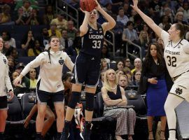 UCONN's Katie Lou Samuelson shoots a three-point shot while Notre Dame's Jessica Shepherd tries to defend during a Women's Final Four game in Tampa, FL. (Image: Chris O'Meara/AP)