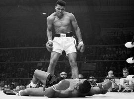 Muhammad Ali standing over Sonny Liston in the first round of their second fight in Lewiston, Maine in 1965. (Image: Getty)