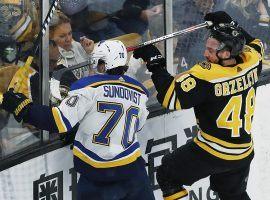 Oskar Sundqvist of the St. Louis Blues and Matt Grzelcyk of the Boston Bruins scrap in the corner of a Stanley Cup Finals game in Boston. (Image: Jim Davis/Boston Globe)