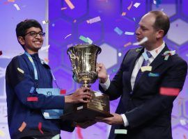Karthik Nemmani, 14, holds the Scripps National Spelling Bee Championship Trophy with Scripps President and Chief Executive Officer Adam Symson after winning last year's contest. (Image: AP)