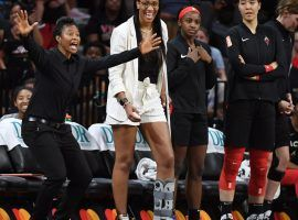 An injury A'ja Wilson watches the Las Vegas Aces from the bench with assistant coach Vickie Johnson (left) and teammates Jackie Young and JiSu Park (right). (Image: Ethan Miller/Getty)