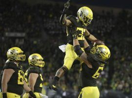 Oregon RB Cyrus Habibi-Likio is picked up by Shane Lemieux after their victory against Cal in Eugene, OR. (Image: Chris Pietsch/AP)