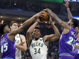 Milwaukee Bucks star Giannis 'Greek Freak' Antetokounmpo (34) drives to the hole against Donovan Mitchell (45) and Royce O'Neale (23) of the Utah Jazz. (Image: Aaron Gash/AP)