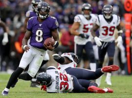 Baltimore Ravens Quarterback Lamar Jackson evades tacklers from the Houston Texans. (Tommy Gilligan/USA Today Sports)