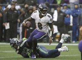 Baltimore Ravens QB Lamar Jackson evades a tackler against the Seattle Seahawks in Seattle WA. (Image: Elaine Thompson/AP)