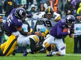 The Northwestern Wildcats QB Aidan Smith is tackled by the Iowa Hawkeyes. (Image: Daniel Bartel/Getty)