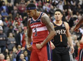 Washington Wizards guard Bradley Beal celebrates a triple-overtime victory over the Phoenix Suns with guard Devin Booker (1) in the background in 2018. (AP Photo/Nick Wass)