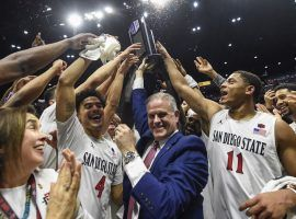 Head coach Brian Dutcher and San Diego State players hold up the Mountain West season championship trophy after defeating New Mexico. (Image: Denis Poroy/AP)