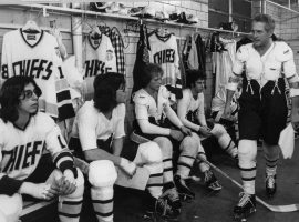 "The Hansen brothers listen to their player/coach Reggie Dunlop (Paul Newman) in ""Slap Shot"" (1977). (Image: AP)"