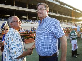 John Sadler, seen here shaking hands with owner Kosta Hronis after their Accelerate won the 2018 Pacific Classic. will sit out the next 15 days. Three of his horses tested positive for banned substances. (Image: Hayne Palmour IV/San Diego Union-Tribune)