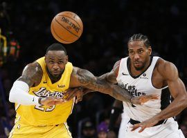 LeBron James (left) and Kawhi Leonard fight for a loose ball at Staples Center. (Image: Ringo H.W. Chiu/AP)
