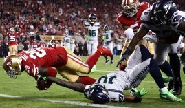 San Francisco 49ers safety Jaquiski Tartt dives over the goal line against the Seattle Seahawks in 2019. (Image: Ezra Shaw/Getty)