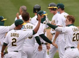 Mark Canha (20) is congratulated by his Oakland A's teammates after a walk-off hit to win in extra innings. (Image: Ezra Shaw/Getty)