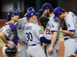 The Dodger gather around Clayton Kershaw en route to his second solid start in the 2020 World Series. (Image: AP)