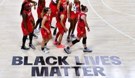 Atlanta Dream players walk by a Black Lives Matter graphic at the Feld Entertainment Center in Florida. Dream co-owner was critical of WNBA's BLM messaging.