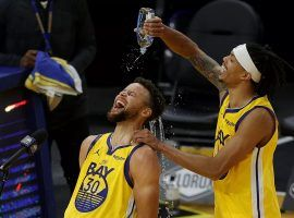 Damion Lee of the Golden State Warriors pours water to cool down a hot Steph Curry after a career-high 62 points. (Image: Porter Lambert/Getty)