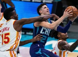 Atlanta Hawks center Clint Capela tries to block Charlotte Hornets guard LaMelo Ball, who would make NBA history as the youngest pro to notch a triple-double. (Image: Suzanne Greenberg)