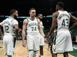 DJ Augustin (12), Pat Connaughton (24), and the Greek Freak (43) assemble during a time out at Fiserv Arena in Milwaukee. (Image: Nick Monroe/USA Today Sports)