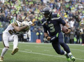 Seattle Seahawks QB Russell Wilson, seen here being chased by a New Orleans Saints defender in a game at CenturyLink Field, indicated he'd waive his no trade clause for four potential teams. (Image: Ted S. Warren/AP)