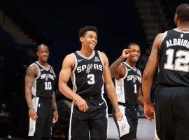 An upbeat Keldon Johnson (3), seen here grinning after hitting a 3-point shot for the San Antonio Spurs, will have to wait another week to play due to the NBA's COVID-19 safety protocols. (Image: David Sherman/Getty)