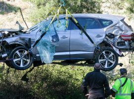 A crane lefts a vehicle after Tiger Woods' rollover car accident in Los Angeles on Tuesday. (Image: Ringo H.W. Chiu/AP)