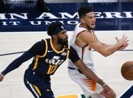 Utah Jazz point guard Mike Conley defense Devin Booker of the Phoenix Suns in Salt Lake City on New Year's Eve. The Jazz and Suns have the top ATS records in the NBA. (Image: Yukai Peng/Getty)