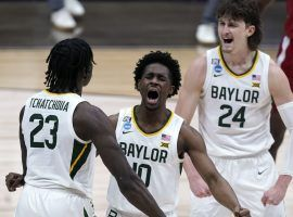 Jonathan Tchamwa Tchatchoua (23), Adam Flagler (10),) and Matthew Mayer (24) celebrate a big play down the stretch for Baylor against Arkansas in March Madness Elite 8 action. (Image: Michael Conroy/AP).