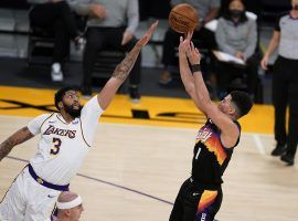 Anthony Davis of the LA Lakers attempts to block a shot on Devin Booker from the Phoenix Suns. (Image: Marcio Jose Sanchez/AP)