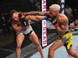 Charles Oliveira (right) punches Michael Chandler (left) on his way to winning the lightweight title in the main event of UFC 262 on Saturday, May 15, 2021. (Image: Josh Hedges/Zuffa)