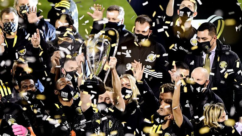 Members of MLS Columbus Crew hold up Philp F. Anschutz Cup after their 2020 MLS Cup victory.