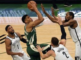 Giannis 'Greek Freak' Antetokounmpo from the Milwaukee Bucks attempts a shot in traffic against Kevin Durant and other members of the Brooklyn Nets. (Image: Getty)