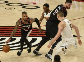 Damian Lillard of the Portland Trail Blazers splits a pair of Denver nuggets defenders, including Nikola Jokic, on a pick-and-roll in Game 4 at the Moda Center in Portland. (Image: Denver Post)