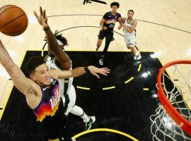 Devin Booker from the Phoenix Suns winds up a dunk against Jrue Holiday of the Milwaukee Bucks in Game 2 of the NBA Finals. (Image: Christian Petersen/Getty)