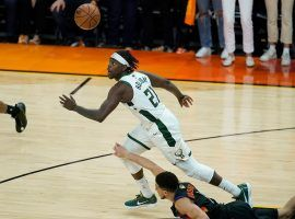 Jrue Holiday from the Milwaukee Bucks eyes a loose ball after forcing Devin Booker of the Phoenix Suns to commit a turnover in the closing seconds of Game 5 of the NBA Playoffs at Phoenix Suns Arena. (Image: Ross D. Franklin/AP)