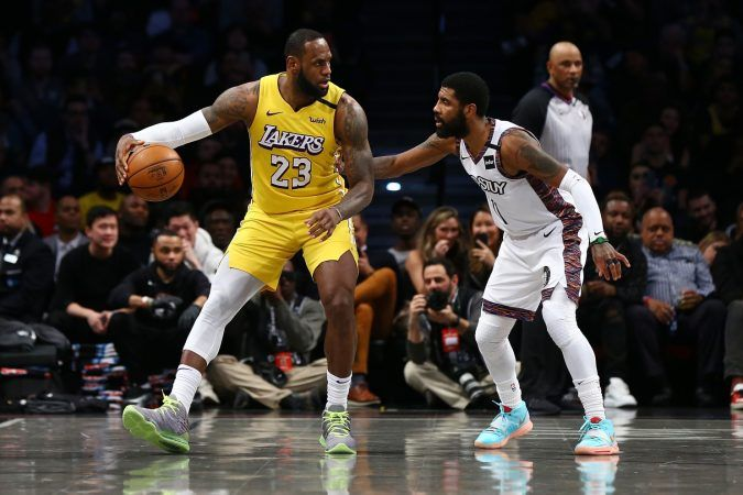 LeBron James from the LA Lakers is guarded by Kyrie Irving from the Brooklyn Nets. Both the Lakers and Nets have the best opening odds to win the NBA championship next year. (Image: Mike Stobe/Getty)