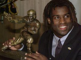 Ricky Williams poses with his 1998 Heisman Trophy. In 2019, Williams sold the trophy for $504,000 in auction (Image: Suzanne Plunket/AP).