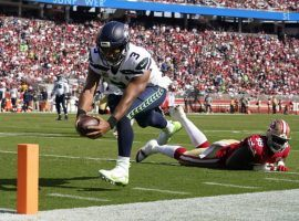 Seattle Seahawks quarterback Russell Wilson dives into the end zone for a touchdown against the San Francisco 49ers. (Image: Tony Avelar/AP)